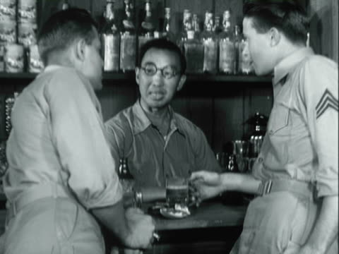 vídeos de stock e filmes b-roll de recreation us servicemen at a bar trying a slot machine, sitting and drinking, and talking with the bartender / south pacific - pacific war
