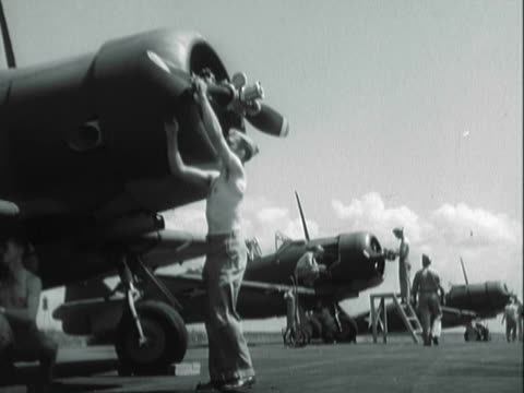 MONTAGE Servicemen on a runway cleaning their propeller aircraft and inspecting the planes