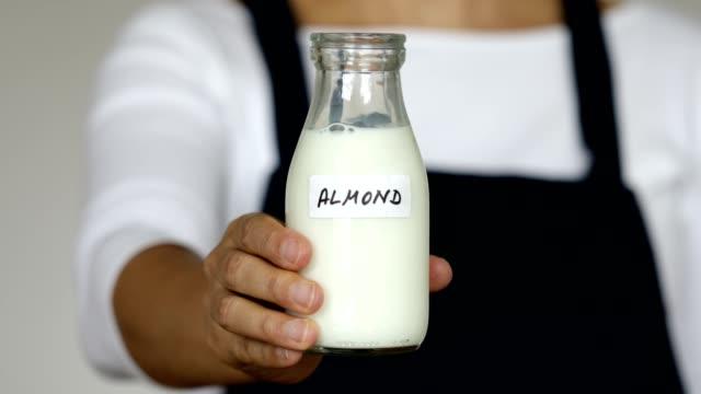 serving almond milk in jar on yellow background - milk jug stock videos & royalty-free footage