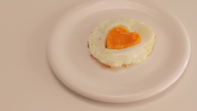 serving an egg fried with a heart yolk - egg yolk stock videos & royalty-free footage