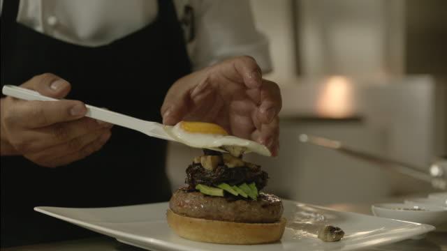 serving an egg into a hamburger - vassoio video stock e b–roll