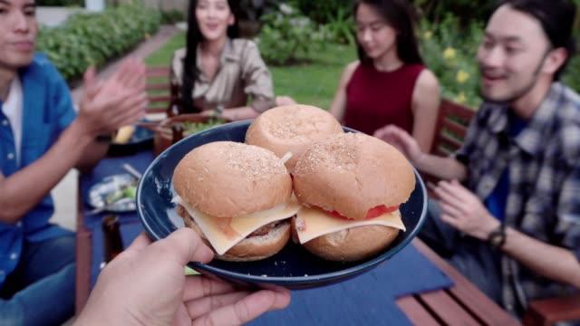 ハンバーガー、自宅屋外バーベキューを持つ友人のグループを提供 - タイ人点の映像素材/bロール