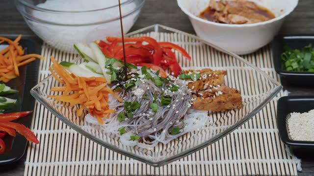 セロファン麺、鶏肉、野菜を提供 - サラダドレッシング点の映像素材/bロール