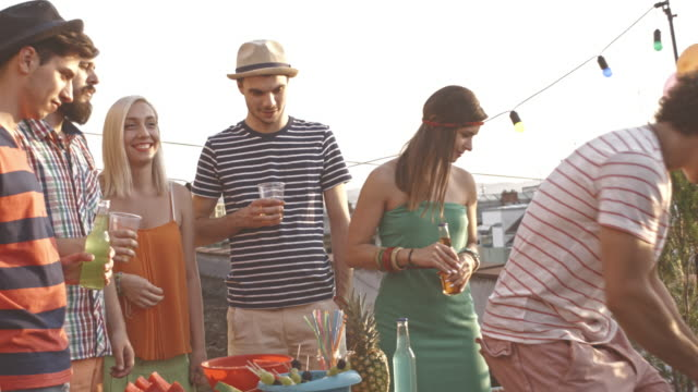 serving drinks to friends during rooftop party - patio stock videos & royalty-free footage