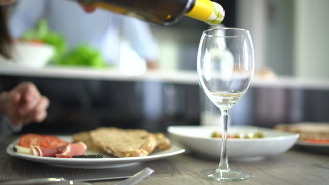Serving glass of wine, bottle and meal n modern kitchen
