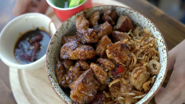 vídeos de stock e filmes b-roll de serving japanese pork steak donburi with fried garlic - ingrediente