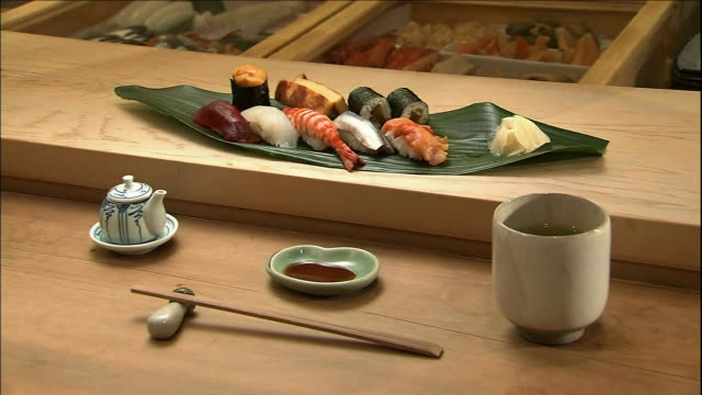 a serving of sushi items lies on the counter of a sushi shop. - nigiri stock videos and b-roll footage