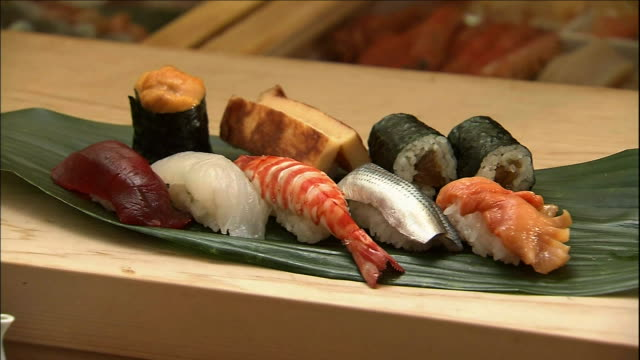 a serving of sushi lies on the counter of a sushi shop. - nigiri stock videos and b-roll footage