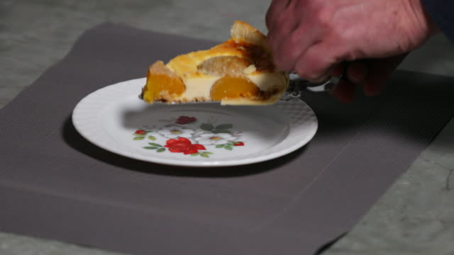 Serving slice of peach cheesecake.