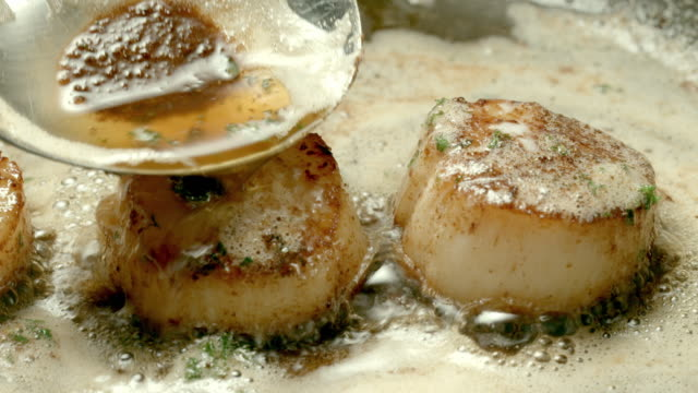 cu serving spoon pours melted butter over scallops cooking in skillet - ホタテ点の映像素材/bロール