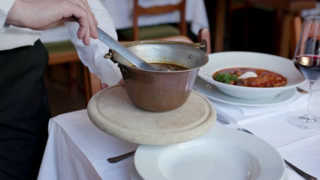 Serving stew with ladle from kettle