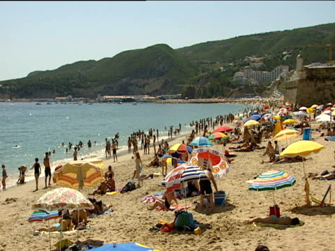 Sesimbra beach crowded with tourists sunbathing and playing in sea