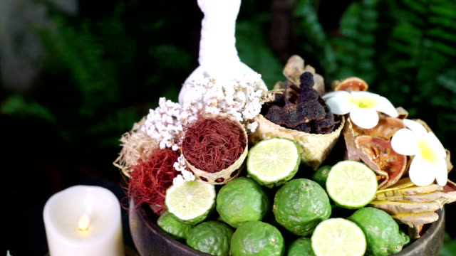 Set of herb and natural spa ingredients herbal compress ball with candles and flowers.