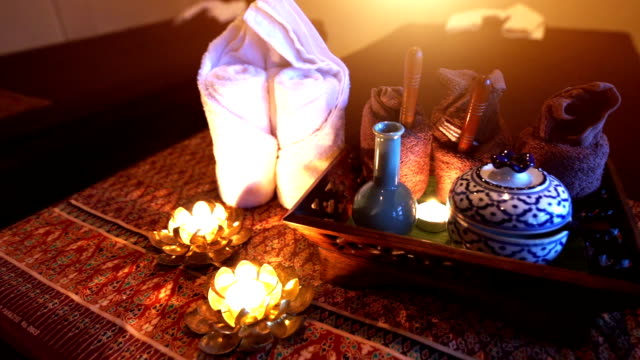 A set of herbal treatments for massage and spa decorated with Frangipani and lighting candles.