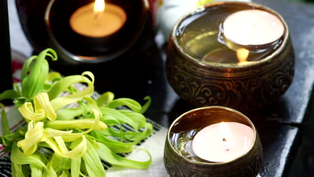 A set of herbal treatments for massage and spa decorated with flower and candles.