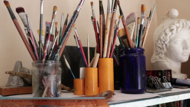 set of paintbrushes and sculpture on table - art studio stock videos & royalty-free footage