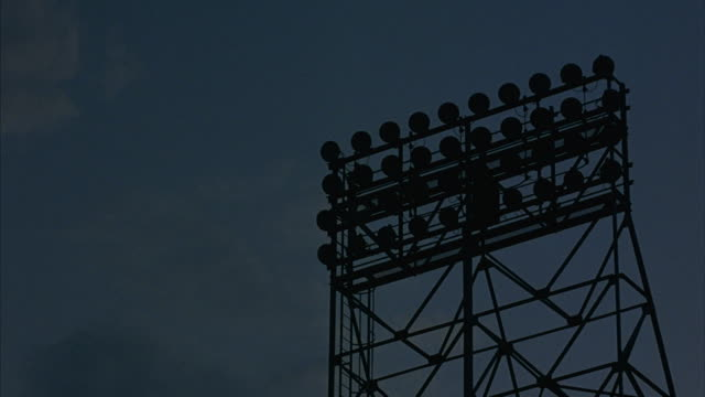 a set of stadium lights turn on. - floodlight stock videos & royalty-free footage