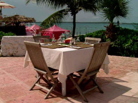 stockvideo's en b-roll-footage met ms,  set outdoor table on terrace,  harbour island,  bahamas - waaierpalm