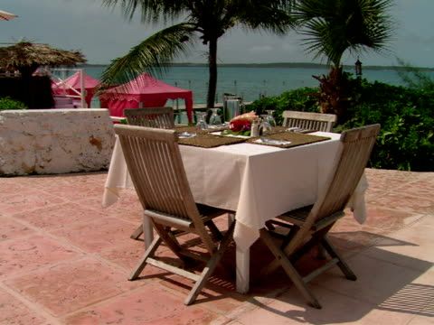 stockvideo's en b-roll-footage met ms,  set outdoor table on terrace of restaurant,  harbour island,  bahamas - waaierpalm