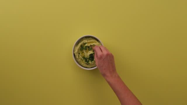 vídeos y material grabado en eventos de stock de setting a dip of avocado hummus down, sprinkling cilantro on top of it and scooping up wit a chip - mojar