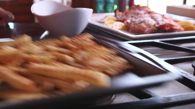 setting pan of fries down cu - wiese stock videos & royalty-free footage