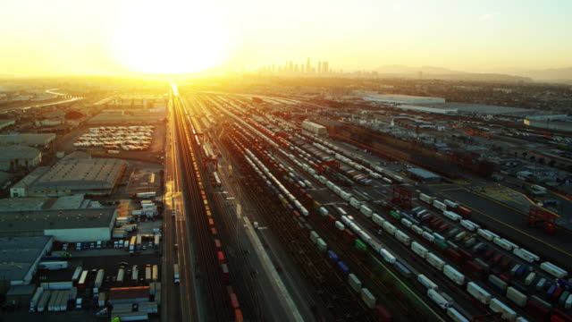 setting sun and downtown la skyline behind vast intermodal yard - drone shot - trasporto merci via terra video stock e b–roll