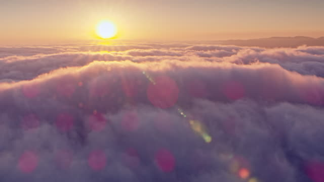 aerial setting sun coloring the fluffy clouds in pink - nuvole video stock e b–roll