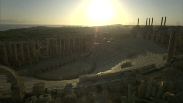 a setting sun glows beyond the ruins of leptis magna. - ancient rome stock videos & royalty-free footage