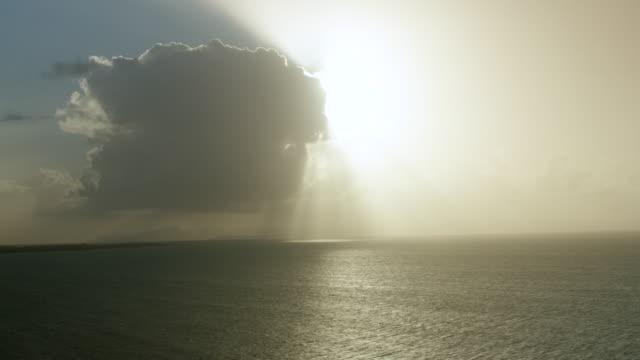 ws pan setting sun hidden behind big cumulus cloud, sea in foreground / vieques, puerto rico, united states - ドラマチックな空模様点の映像素材/bロール