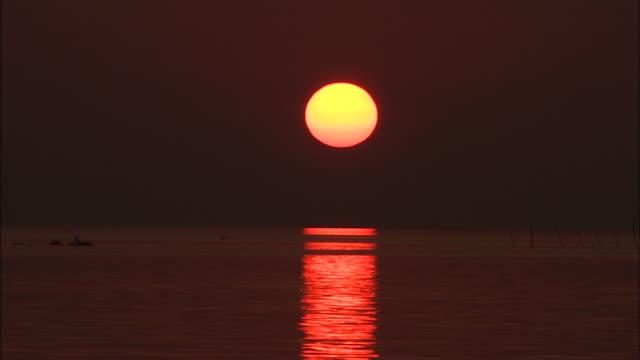 setting sun in dark sky at lake shinji, shimane, japan - shimane prefecture stock videos & royalty-free footage
