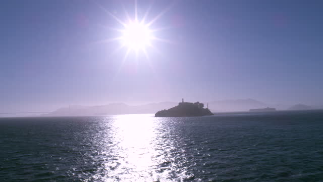 setting sun over alcatraz island with bay bridge and treasure island in the distance; bright reflection on the water; large cargo boat in the... - san francisco bay stock videos & royalty-free footage