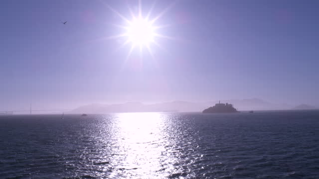 setting sun over alcatraz island with bay bridge and treasure island in the distance; bright reflection on the water - san francisco bay stock videos & royalty-free footage