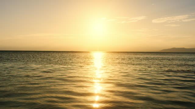SLO MO Setting sun reflecting on the sea surface