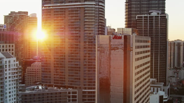 setting sun shining between office buildings and condo towers in brickell, miami at sunset - drone shot - aerial view stock videos & royalty-free footage