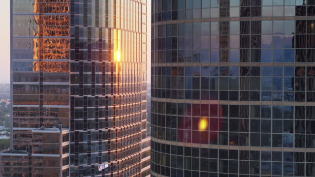 setting sun shining on curved modern office towers - drone shot - century city stock videos & royalty-free footage