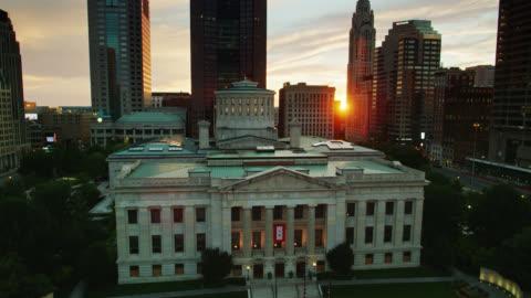 vidéos et rushes de coucher le soleil brillant à travers les gratte-ciel de columbus du centre-ville sur le capitole de l'état de l'ohio - ohio