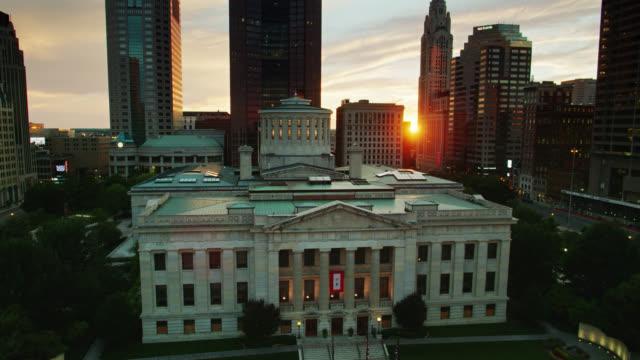 setting sun shining through downtown columbus skyscrapers on ohio state capitol - ohio video stock e b–roll