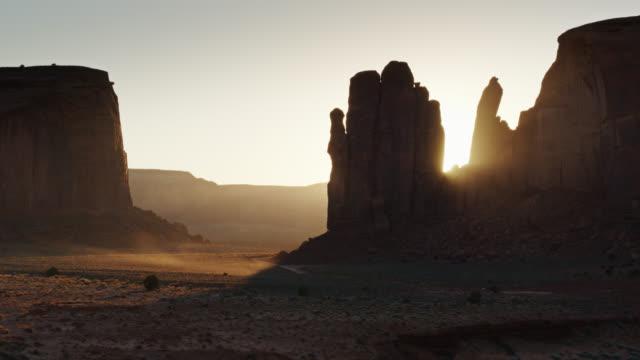 vídeos de stock e filmes b-roll de setting sun shining through monument valley - drone shot - monument valley