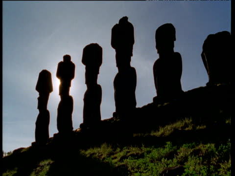 stockvideo's en b-roll-footage met setting sun silhouettes line of moai monolithic statues - polinesische cultuur