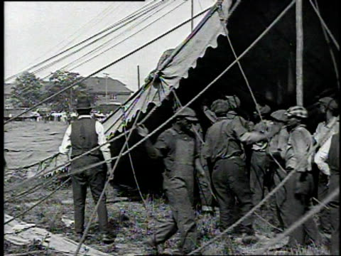 setting up a circus people in front of and on top of railroad freight car with 'iron mountain' on side / harnessed horses are led from box car wagons... - festzelt stock-videos und b-roll-filmmaterial