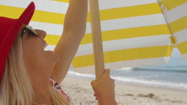 vídeos de stock, filmes e b-roll de instalando-se na praia - chapéu de sol