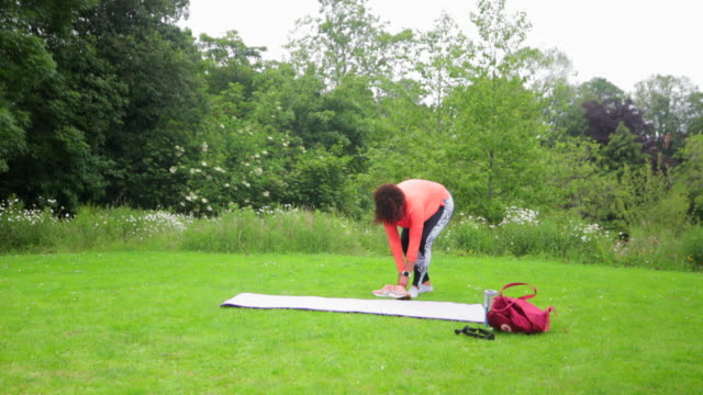 setting up her yoga mat - lotus position stock videos & royalty-free footage