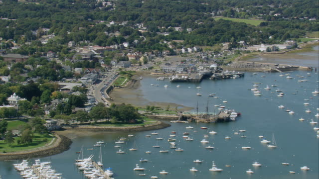 aerial settled coastline and harbor dotted with many pleasure boats / plymouth, massachusetts, united states - massachusetts stock-videos und b-roll-filmmaterial