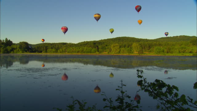 WS, Seven colorful hot air balloons floating in blue sky over forest and still lake, Queshee, Vermont, USA