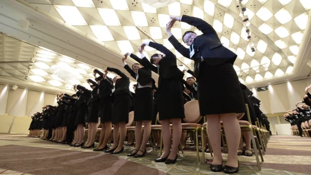 seven i holdings co new employees attend an initiation ceremony in tokyo japan on thursday march 19 new employees stretch during an initiation... - 人材採用点の映像素材/bロール