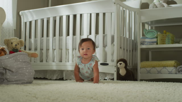 a seven-month-old asian baby with dark eyes, dressed in a simple cover, sits, then crawls in front of her crib, toward camera. - 這う点の映像素材/bロール