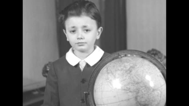 vidéos et rushes de seven-year-old patrick henry schiavone stands at a globe in the living room of a house; his father sits on a loveseat behind him, holding a book and... - canal de suez
