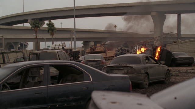 Several abandoned cars and a tank burn on a freeway.