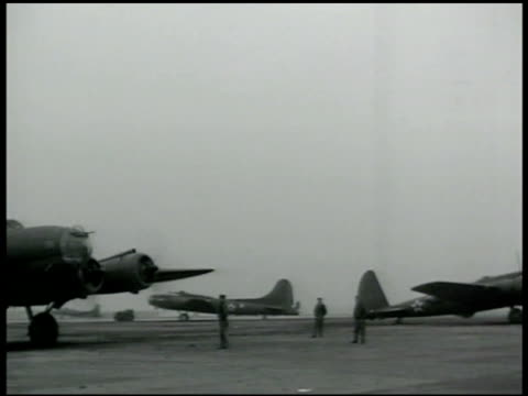 several b17 flying fortress bomber airplanes on airfield four men carrying bomb toward bomber men unloading bombs from cart w/ b17 bg world warii wwii - beladen stock-videos und b-roll-filmmaterial
