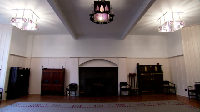 several cabinets line a wall beside a fireplace in the glasgow school of art. available in hd. - charles rennie mackintosh stock videos and b-roll footage